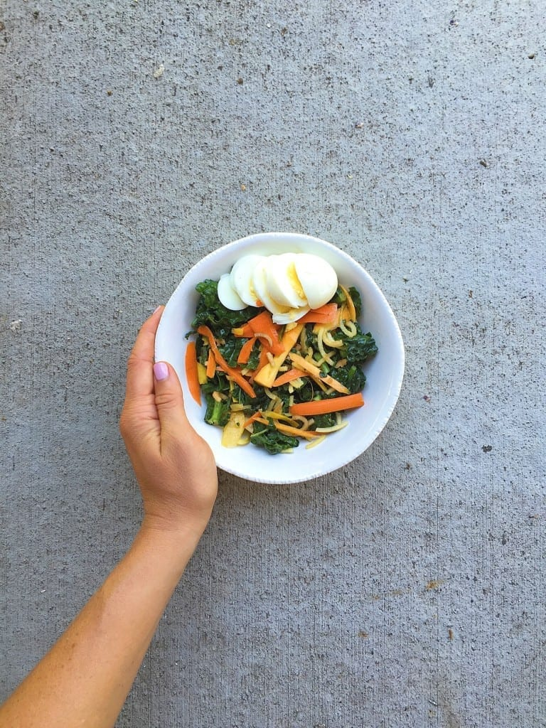 massaged kale and carrot salad with egg_and hand